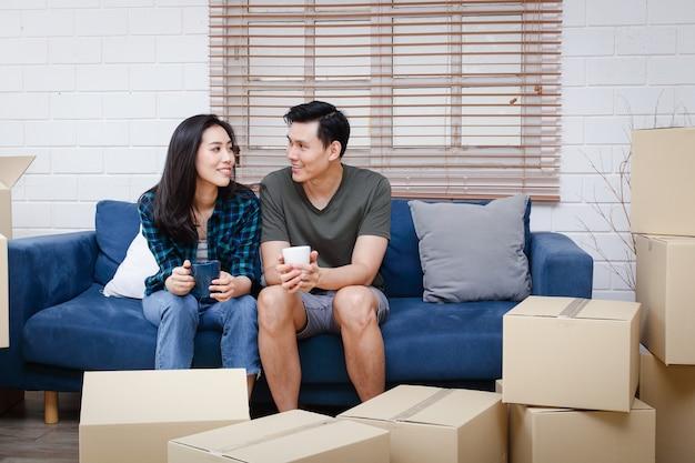 Азиатская пара сидит на диване и только что переехала в новый дом, чтобы создать теплую семью. Premium Фотографии