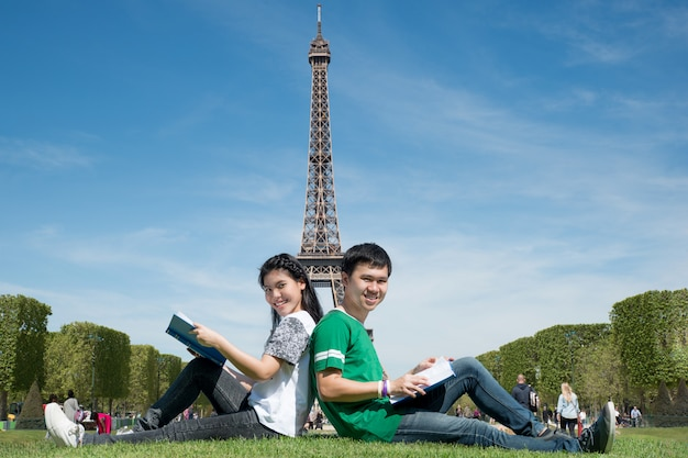 Asian couple student reading book together at outdoors park near eiffel tower in paris, france. Premium Photo