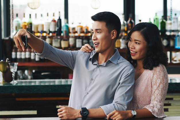 Asian couple taking selfie on smartphone in bar Free Photo