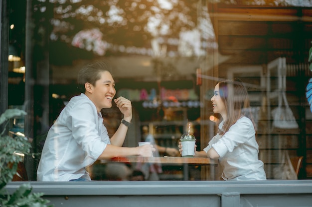Asian couple talking happily in the cafe during the daytime. Premium Photo