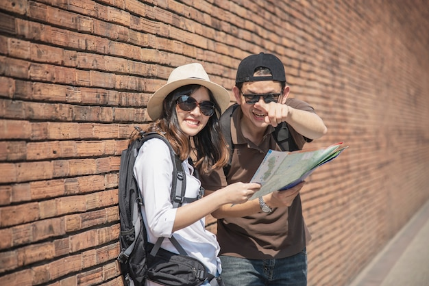 Asian couple tourist holding city map crossing the road Free Photo