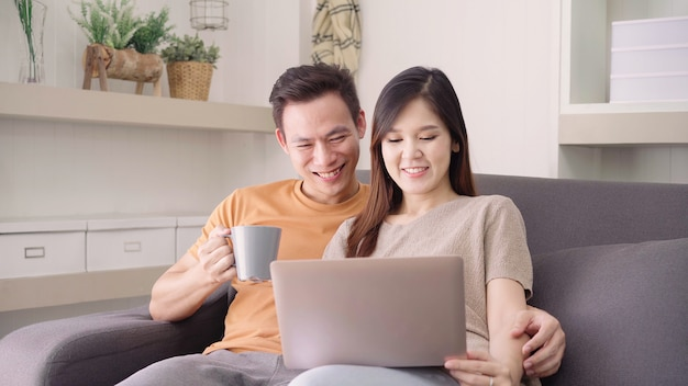 Free Photo   Asian couple using laptop and drinking warm cup of coffee in  living room at home, sweet couple enjoy