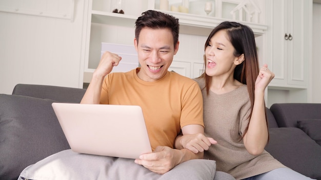 Asian couple using laptop for search web in living room at home Free Photo