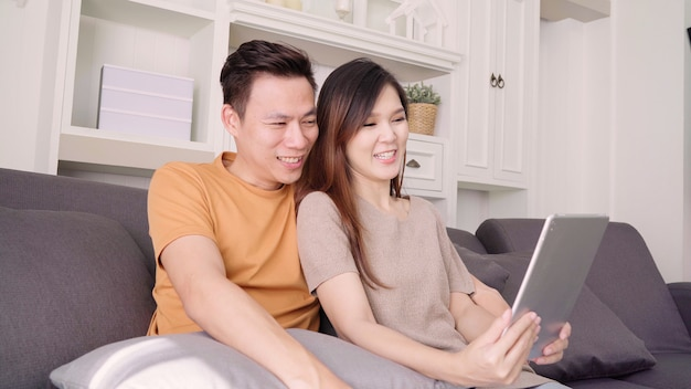 Asian couple using tablet video call with friend in living room at home Free Photo