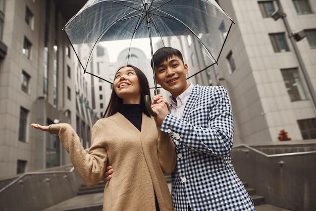 Asian couple walking together under umbrella. Premium Photo