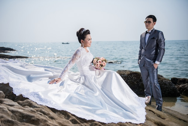 Asian couple wearing wedding dress and suit for beach wedding ...