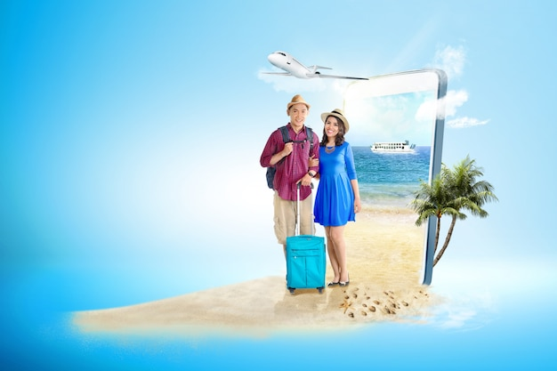 Asian couple with suitcase bag and backpack standing on the beach Premium Photo