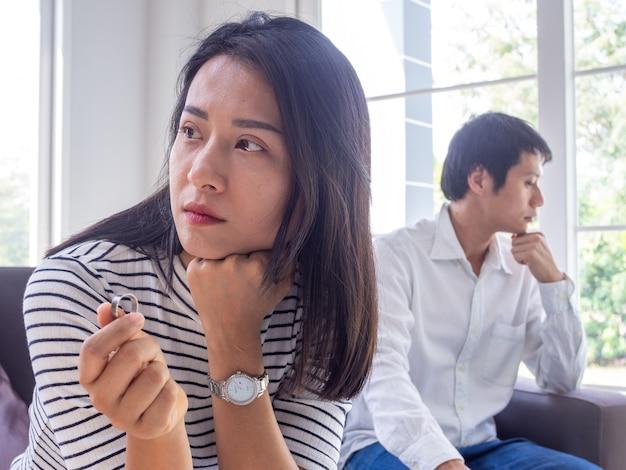 У азиатских пар возникают конфликты. жена снимает обручальное кольцо из-за стресса мужа и семейных проблем. Premium Фотографии
