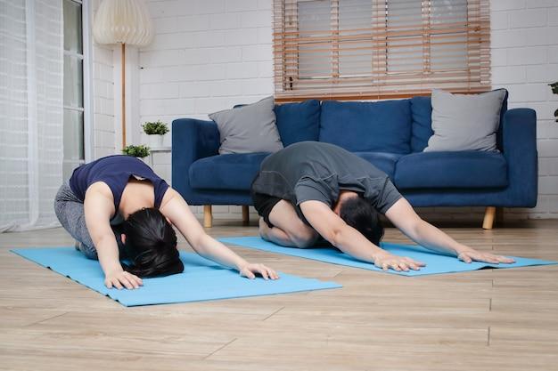 Азиатские пары тренируются вместе дома в гостиной. для поддержания хорошего здоровья и социальной дистанции во время covid 19 Premium Фотографии