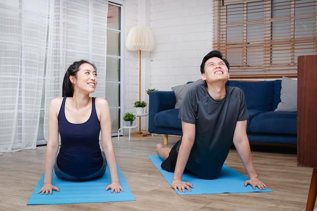 Азиатские пары тренируются вместе дома в гостиной. Premium Фотографии