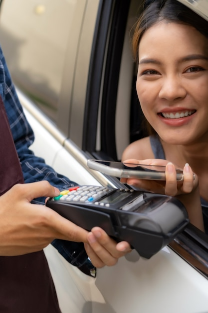 Азиатский клиент совершает бесконтактный мобильный платеж drive thru Premium Фотографии