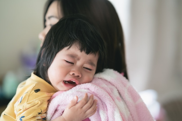 Asian cute baby crying at mom on hands Premium Photo