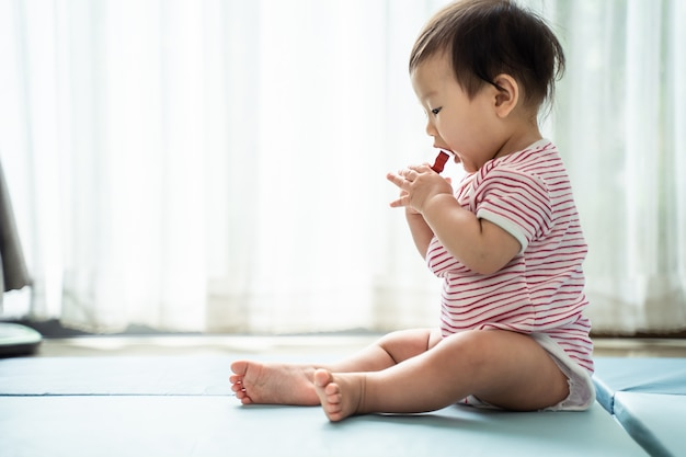 Asian cute baby holding toy and trying to eat it, put into mouth, sitting at home. Premium Photo