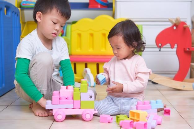 아시아 귀여운 오빠와 여동생이 집에서 놀이방에서 장난감 블록을 가지고 노는 재미, 어린 아이를위한 교육 장난감, 형제 자매의 유대, 놀이를 통해 배우기 프리미엄 사진