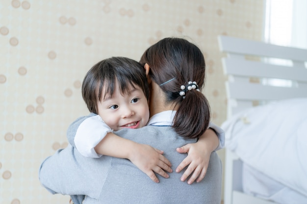 Asian cute boy smiling with happily and hugging with mother at home, copy space, family concept Free Photo