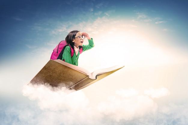안경 및 배낭 푸른 하늘이 책에 앉아 아시아 귀여운 소녀 프리미엄 사진