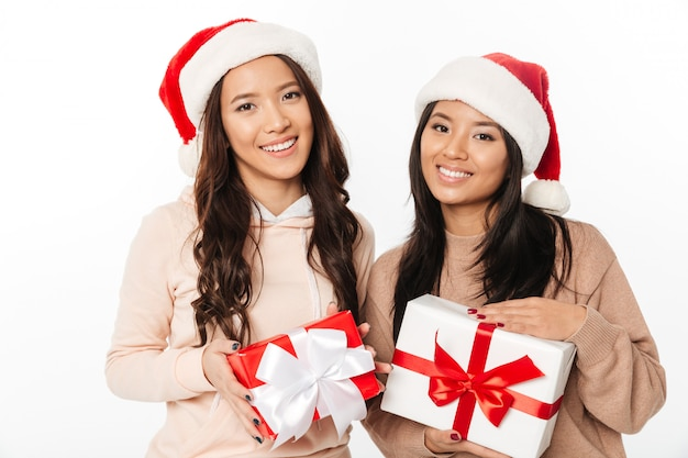 Asian cute ladies sisters wearing christmas santa hats Free Photo