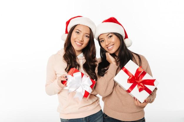 クリスマスサンタ帽子をかぶっているアジアのかわいい女性姉妹 無料写真