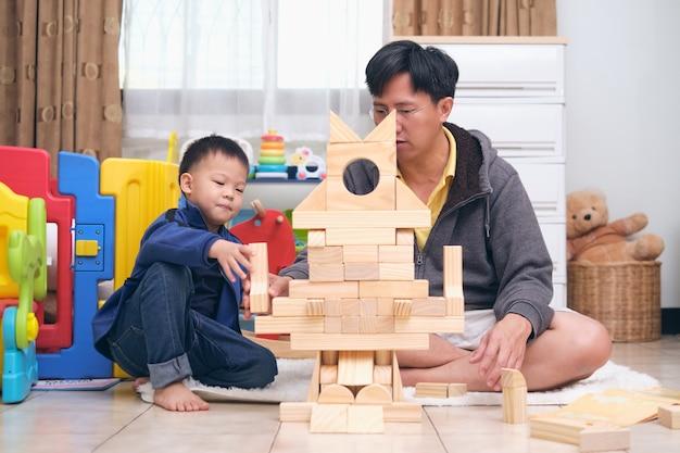 Азиатские папа и сын веселятся, играя с деревянными игрушками из строительных блоков дома, счастливый отец и милый маленький азиатский мальчик из детского сада проводят время вместе Premium Фотографии