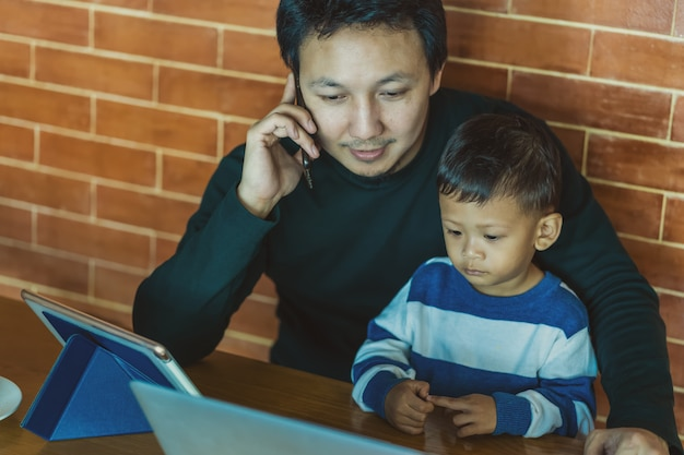 Asian dad with son are looking the cartoon via technology laptop together with phone calling Premium Photo