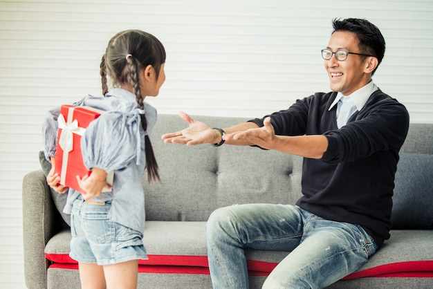 アジアの娘が父親にプレゼントを差し出します。父の日のためのコンセプトサプライズギフトボックス。 Premium写真