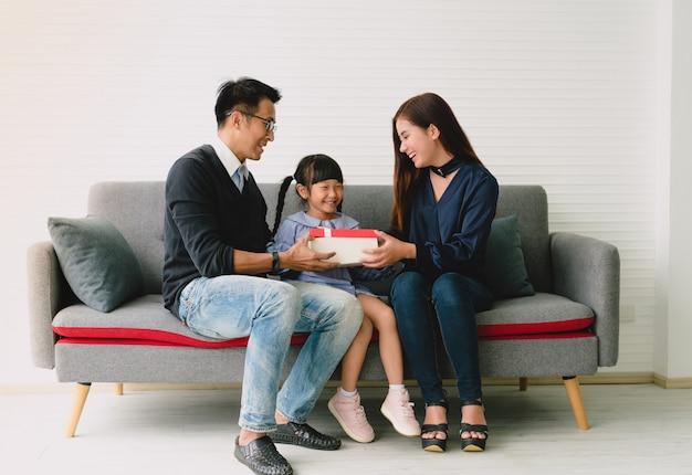 アジアの娘が父と母とのプレゼントを開催します。 Premium写真