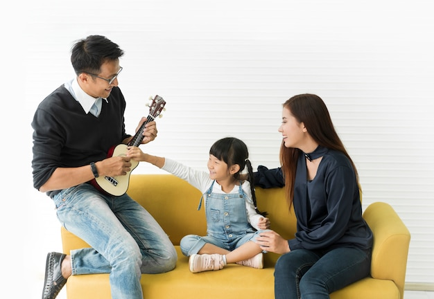 Asian daughter playing guitar and singing with father and mother on sofa in living room. Premium Photo
