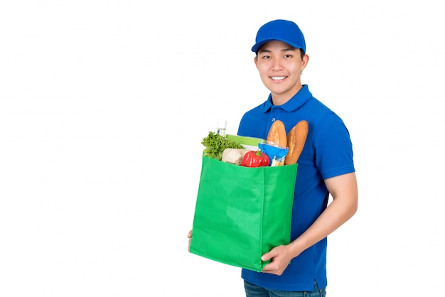 Asian delivery man carrying groceries in green reusable bag Premium Photo