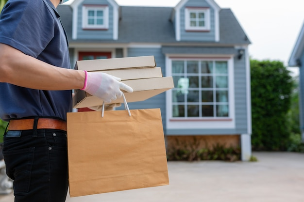 Азиатский работник доставляющий покупки на дом в пакете владением перчатки маски маски футболки голубой крышки бумажном для на вынос еды. концепт-сервис карантинного вируса пандемического коронавируса [covid-19] Premium Фотографии
