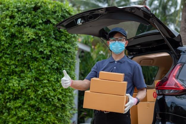 Азиатский работник доставляющий покупки на дом в владении перчатки маски футболки голубой крышки равномерном держит коробку пакета. концепт-сервис карантинного вируса пандемического коронавируса [covid-19] Premium Фотографии