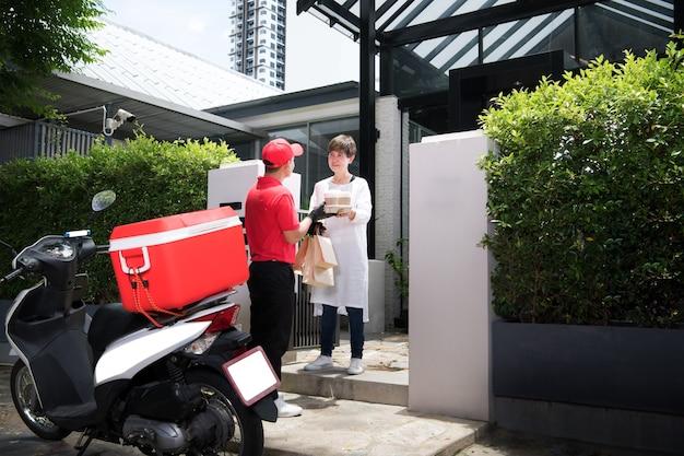 Азиатский курьер в красной форме доставляет сумку с продуктами, фруктами, овощами и напитками женщине-получателю дома Premium Фотографии