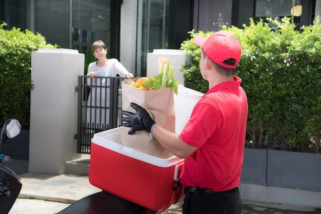 Азиатский курьер в красной форме доставляет коробку с продуктами, фруктами, овощами и напитками женщине-получателю дома Premium Фотографии