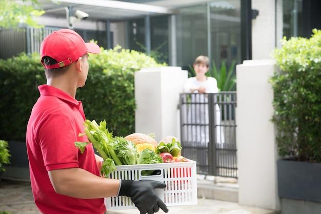 Азиатский курьер в красной форме доставляет коробку с продуктами, фруктами, овощами и напитками женщине-получателю Premium Фотографии