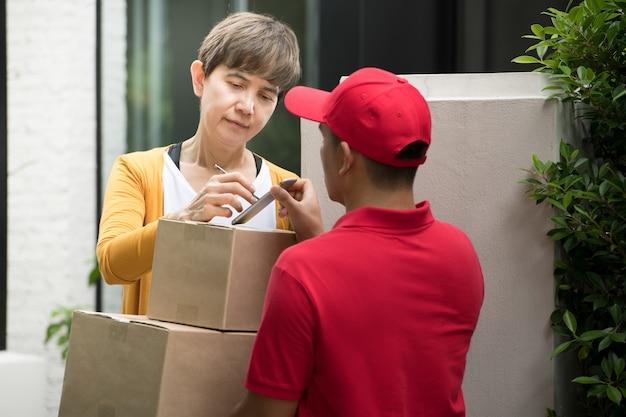 스마트 장치에서 패키지를 받기 위해 수신자 기호로 집에서 여자 수신자에게 소포 상자를 제공하는 빨간색 제복을 입은 아시아 배달 남자 프리미엄 사진