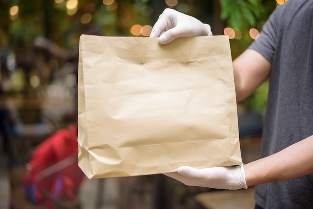 An asian delivery man is wearing face mask, holding grocery bag , safety home delivery concept Premium Photo