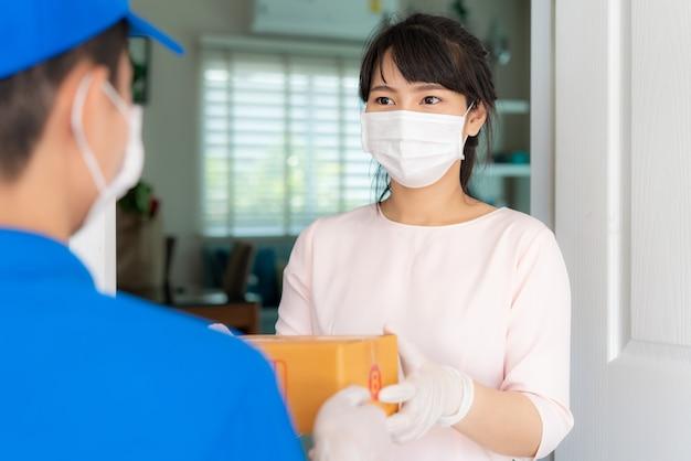 Азиатский курьер, носящий маску и перчатку в синей форме с картонными коробками в передней части дома и женщина, принимающая доставку коробок от доставщика во время вспышки covid-19. Premium Фотографии