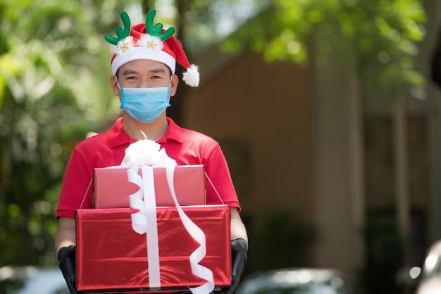 Азиатский курьер в маске и перчатках в красной форме и рождественской шляпе доставляет подарки и подарочные коробки во время вспышки covid-19 на рождественский фестиваль Premium Фотографии