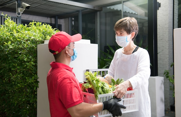 Азиатский курьер в маске и перчатках в красной форме доставляет коробку с продуктами Premium Фотографии