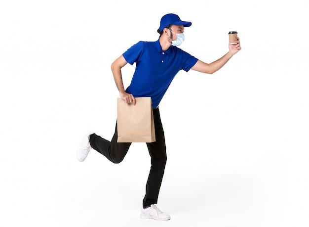 Uomo di consegna asiatico che indossa la maschera per il viso in uniforme blu in esecuzione con sacchetto di carta e caffè da asporto isolato su uno spazio bianco. servizio di consegna espressa durante covid19. Foto Gratuite
