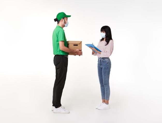 소포 상자 녹색 제복을 입은 얼굴 마스크를 쓰고 아시아 배달 남자는 흰색 위에 여자 Costumer에 제공합니다. 무료 사진