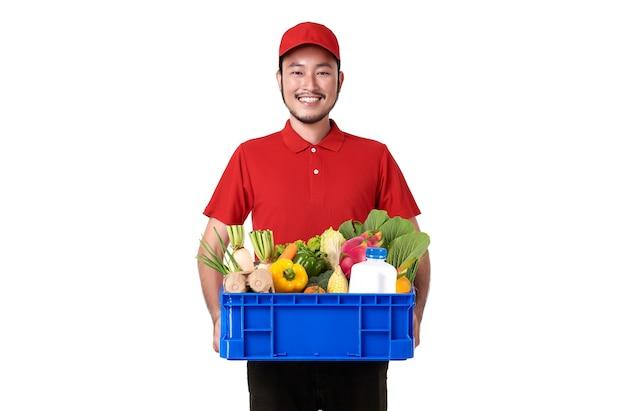 白い壁に分離された生鮮食品のバスケットを保持している赤い制服を着ているアジアの配達人。 無料写真