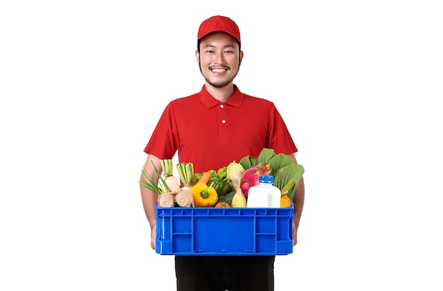Asian delivery man wearing in red uniform holding fresh food basket isolated over white wall. Free Photo