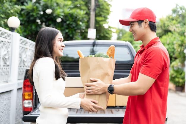 Азиатский курьер в красной форме, красная шляпа держит бумажный пакет Premium Фотографии