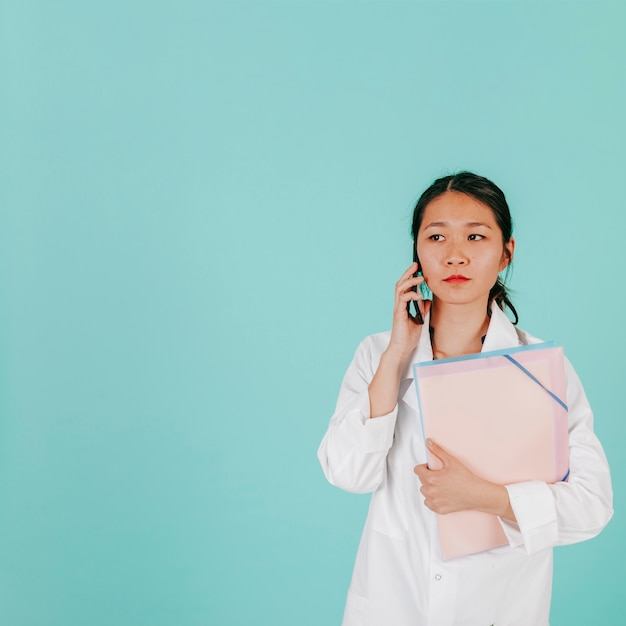 Asian doctor answering phone call Free Photo
