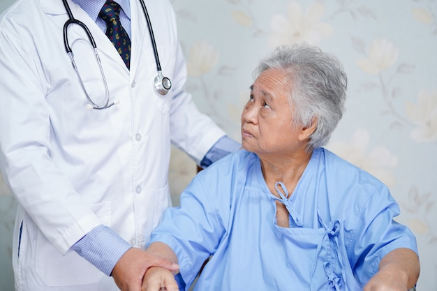 Asian doctor care, help and support senior or elderly old lady woman patient at hospital ward Premium Photo