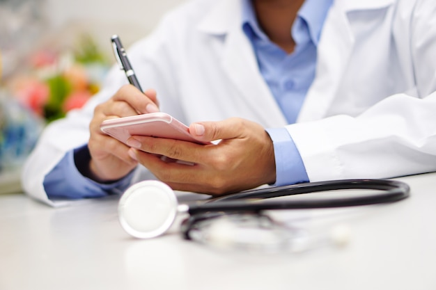 Asian doctor holding mobile phone to communicate about work at modern office. Premium Photo