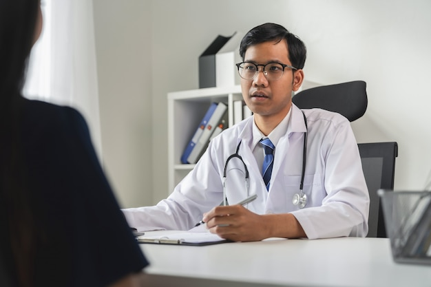Asian doctor is report the symptoms and advising the patient. Premium Photo
