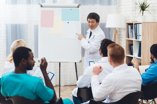 Asian doctor shares experience with colleagues. Premium Photo