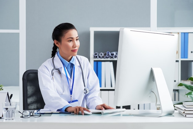 Asian doctor with stethoscope around neck sitting in office and working on computer Free Photo