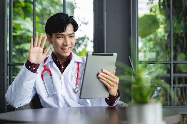 Азиатские врачи используют планшеты, чтобы приветствовать пациентов с помощью видеозвонка. новый медицинский стандарт может лечить, отслеживать болезни и консультировать удаленных пациентов с помощью технологии интернета вещей. Premium Фотографии
